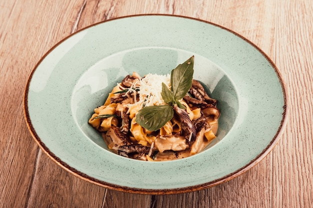 Italian pasta with meat sauce in a plate on a wooden background top view