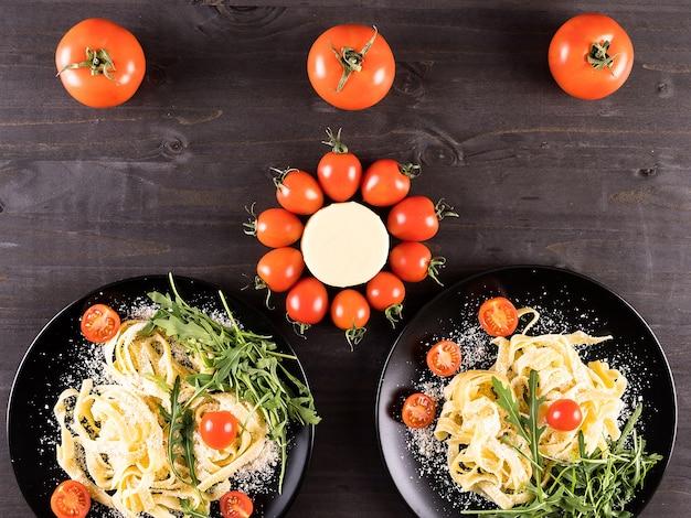 木の板にパルメザンチーズを添えたイタリアンパスタ