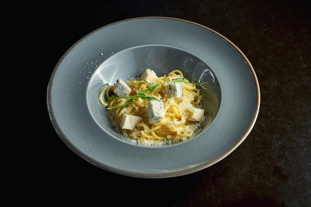 Итальянская паста с тремя видами сыра пармезан, бри и голубой плесенью в серой тарелке на черном фоне. крупным планом, выборочный фокус