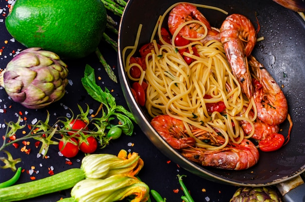 Italian pasta with tiger prawns or shrimps with vegetables