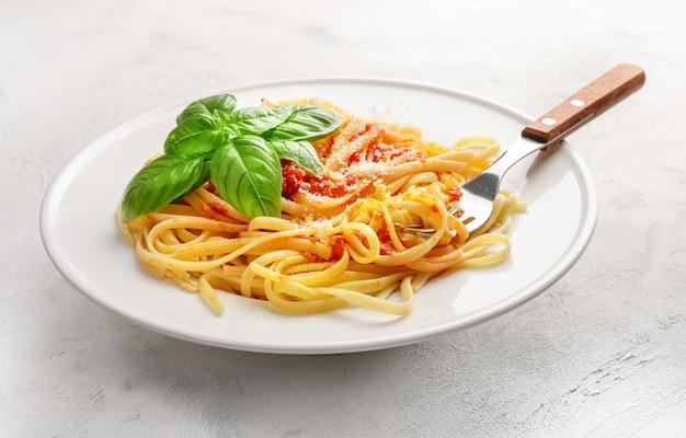 Итальянская паста с помидорами, сыром пармезаном и базиликом на белой тарелке на белом.