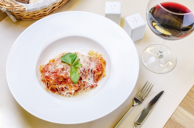 Italian pasta with tomatoes, cheese and a sprig of basil