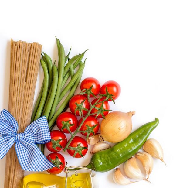 コピースペースと白い背景の上のトマト、緑豆、タマネギ、ニンニク、オリーブオイルのイタリアンパスタ