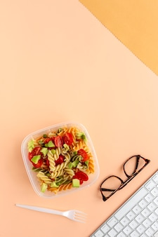 Italian pasta with vegetables on office desk with keyboard and glasses
