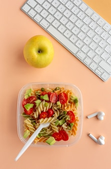 Italian pasta with vegetables on office desk with keyboard