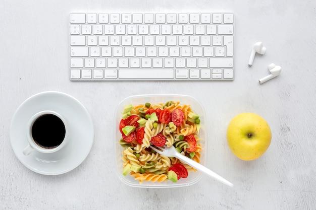Итальянская паста с овощами на офисном столе с клавиатурой