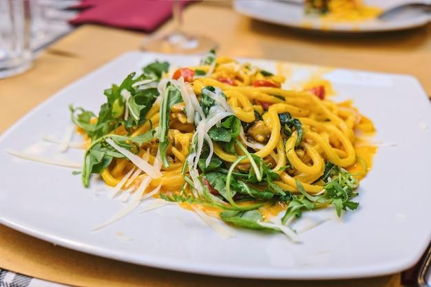 Итальянская паста с овощами, тыквой и рукколой крупным планом