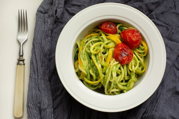 Italian pasta with zucchini noodles with avocado sauce pesto and roasted tomato in white plate. top view gray textile . healthy food .