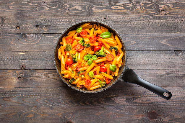 Итальянская паста пенне в томатном соусе и с разными овощами на деревянном столе