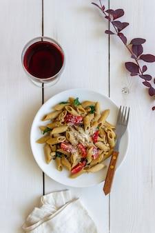 トマト、ほうれん草、パルメザンチーズ、ニンニク、ナッツのイタリアンペンネパスタ。健康的な食事。ベジタリアンフード。
