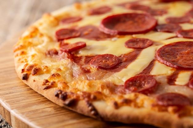 木製のテーブルにイタリアのペパロニピザ