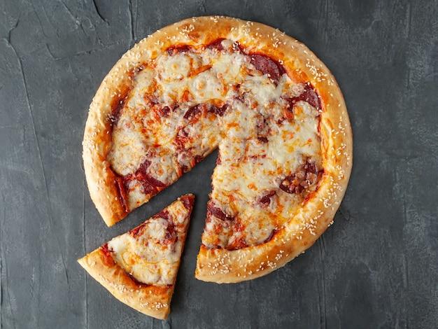 이탈리안 페퍼로니 피자. 페퍼로니 소시지, 토마토 소스, 모짜렐라 치즈, 설구니, 파마산 치즈와 함께. 피자에서 한 조각이 잘립니다. 위에서 볼. 회색 콘크리트 배경에. 외딴.