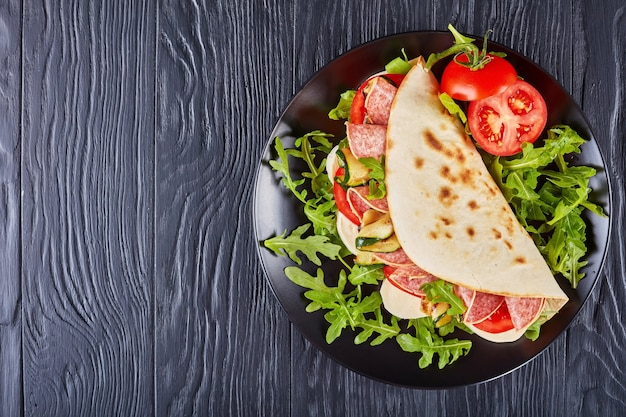 Italian piadina with mozzarella, tomato, salami slices, grilled zucchini and arugula on a black plate on a black wooden table
