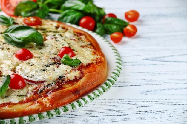 軽い木製の背景にトマト、チーズ、バジルのイタリアンパイ。イタリアンマルゲリータピザ