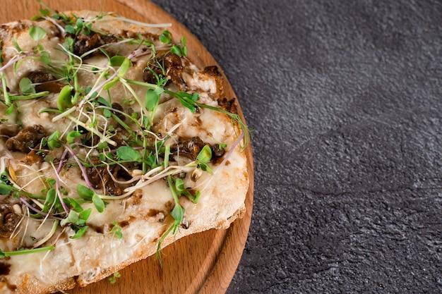 어두운 배경에 프랑스 에스카르고 포도 달팽이를 넣은 이탈리아 핀사 로마나. 달팽이, 치즈, 마이크로 그린 핀사. 이탈리아 미식가 요리.