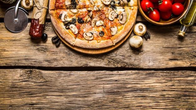 이탈리아 피자와 다양한 재료-고기, 버섯, 토마토, 올리브 오일. 나무 배경.