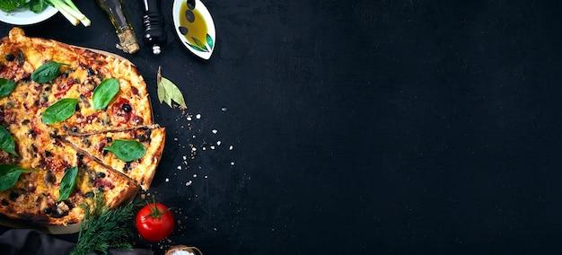 暗い背景にイタリアンピザとピザ料理の材料。トマト、オリーブオイル、スパイス。