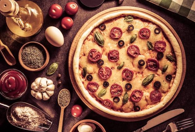 古い表面の背景でイタリアンピザ