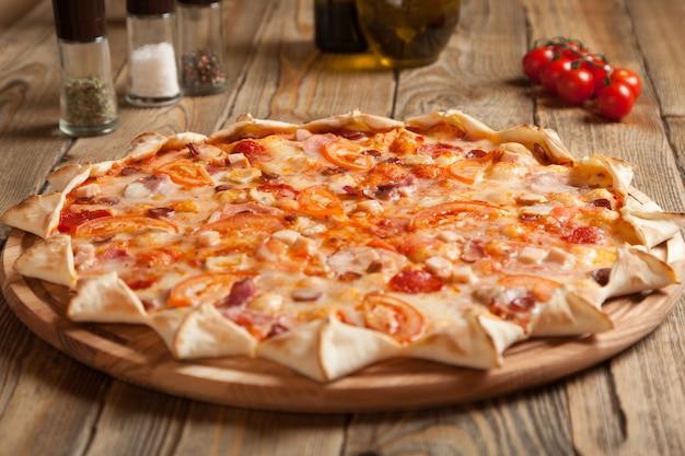 木製のテーブルにイタリアンピザ「バイエルン」。近くにはスパイスとオリーブオイルの入った容器があります。それらの近くにチェリートマトがあります。ピザは6つの部分にカットされます。エッジの伝統的な形はありません。