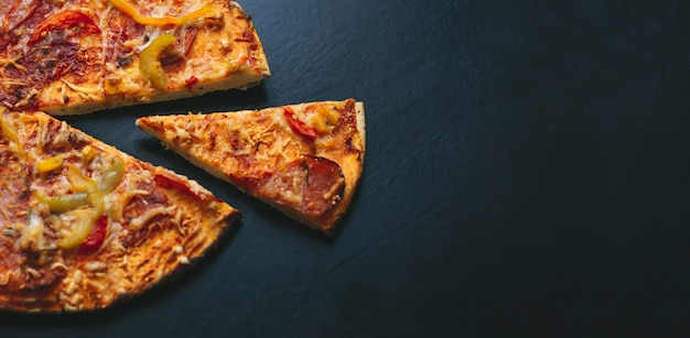 Italian pizza on a black background with top view. space for text