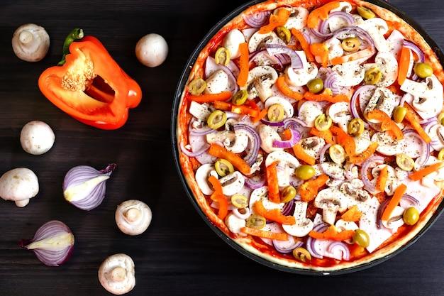 Итальянская пицца крупным планом на темном деревянном фоне с грибами и овощами, вид сверху