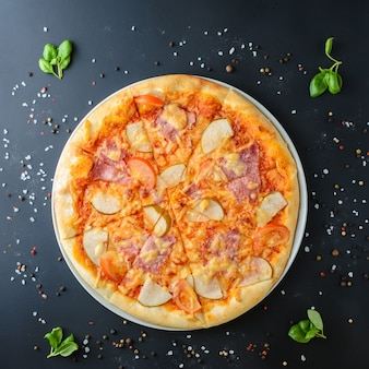 Italian pizza on a dark background, top view