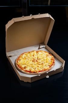 イタリアのピザの配達。モッツァレラチーズ、パルメザンチーズ、チーズを使ったおいしいオーブン焼きピッツェリア料理を段ボール箱でお届けします。夕食にオーブンで調理したおいしいテイクアウトのファーストフード。