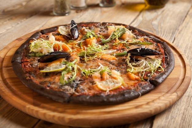 木製のテーブルに黒い生地とシーフードを添えたイタリアンピザ「ディマーレ」。スパイスとオリーブオイルのボトルが入った容器。その上にエビ、レモン、ルッコラ、レタス、ムール貝の開いた殻を置きます。