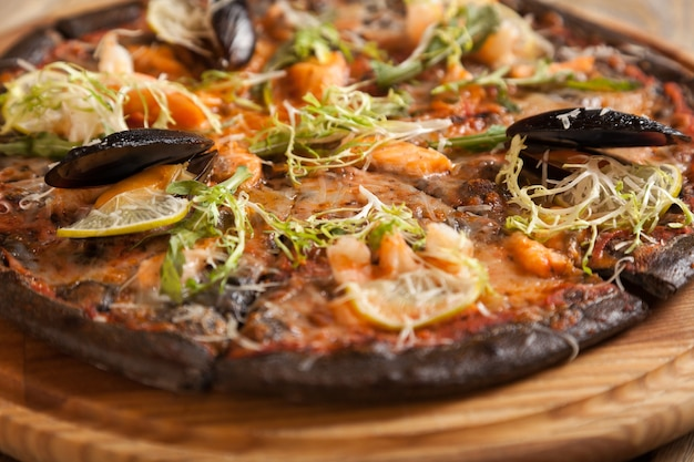 Italian pizza di mare with black dough and seafood on wooden table