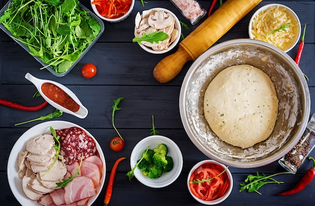 Italian pizza.  dough and pizza ingredients. dough, cheese, tomatoes, broccoli, mushrooms, salami, ham, chicken fillet or bakery cooking. top view