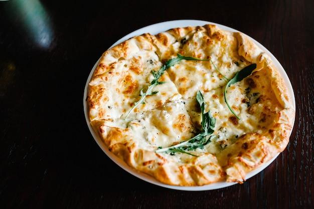 茶色の木製の机の表面にルッコラとイタリアンピザ4チーズ