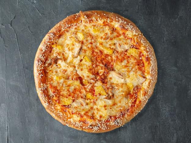 이탈리안 피자. from 치킨 필레, 파인애플, 토마토 소스, 모짜렐라 치즈, 설구니 치즈. 넓은 쪽. 위에서 볼. 회색 콘크리트 배경에. 외딴.