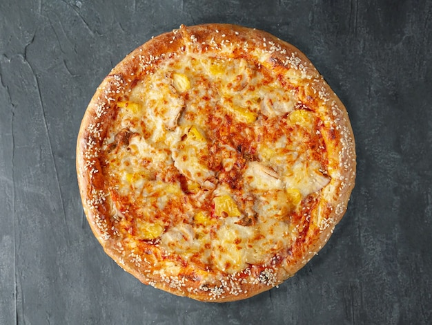 Italian pizza. from chicken fillet, pineapple, tomato sauce, mozzarella cheese and sulguni cheese. wide side. view from above. on a gray concrete background. isolated.