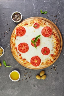 Italian pizza and ingredients for cooking on a black concrete background. tomatoes, olives, basil and spices. copy space for text.