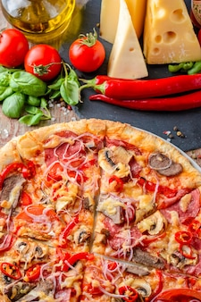 Italian pizza and ingredients on a wooden background, top view