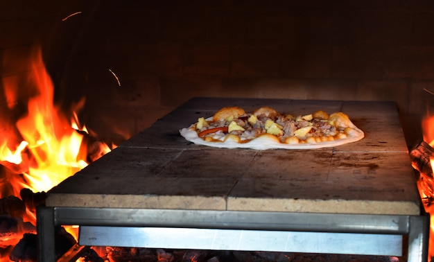 Italian pizza is cooked in a traditional wood-fired oven