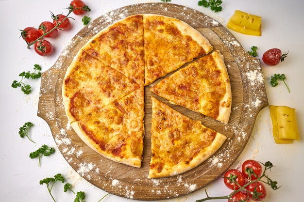 Итальянская пицца маргарита с моцареллой и томатным соусом на деревянном столе, помидорами и сыром на заднем плане
