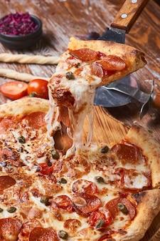 나무 테이블에 이탈리아 피자입니다. 치즈 스트레칭과 함께 뜨거운 피자 조각입니다.