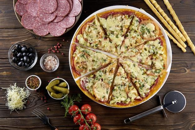 周りの食材を使った木製のテーブルでイタリアのピザ。トップビューのフラットレイ