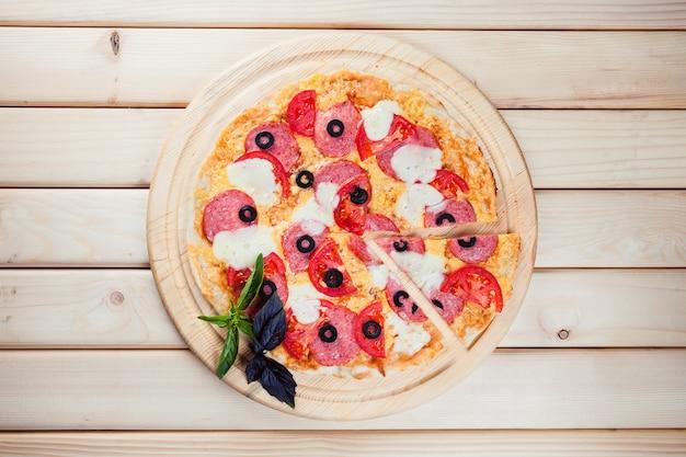 木製のテーブルでイタリアのピザ