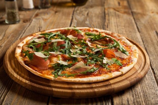 イタリアのピザ「パルマ」は美しい木製のテーブルの上にあります。ピザの上に薄くスライスしたハム、ルッコラ、パルメザンチーズのスライス。近くにはスパイスとオリーブオイルの入った容器があります。
