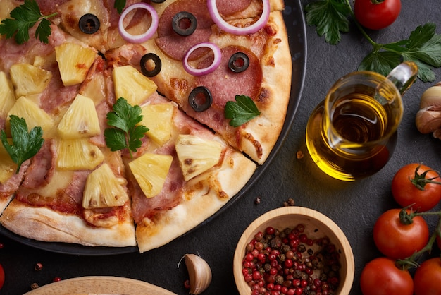 Italian pizza and pizza cooking ingredients on black concrete background.