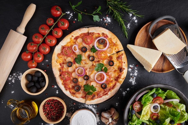 Italian pizza and pizza cooking ingredients on dark stone surface