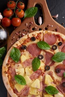 Pizza italiana e ingredienti da cucina pizza sul tagliere di pizza in legno. sfondo di pietra scura.