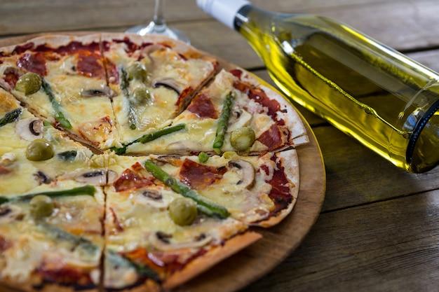 ワインボトル付きのピザトレイで提供されるイタリアのピザ