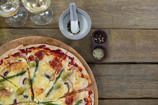 나무 판자에 와인 잔과 재료와 피자 트레이에 이탈리아 피자 제공