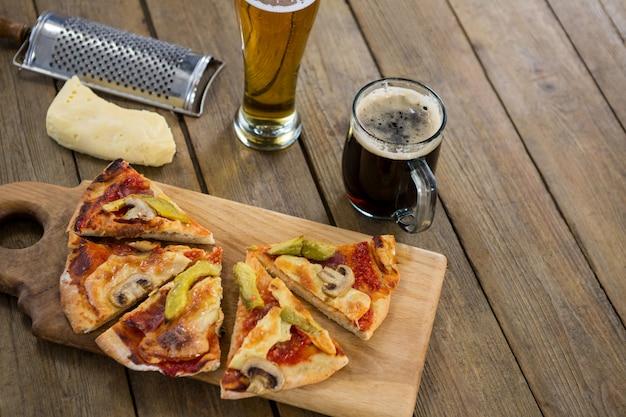 ビールジョッキとグラスをまな板で提供するイタリアのピザ