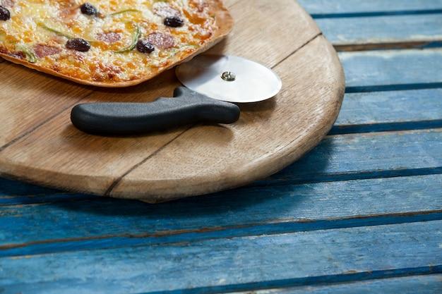 Итальянская пицца подается на подносе пиццы с резаком