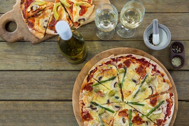 나무 판자에 와인 잔과 재료와 함께 제공되는 이탈리아 피자