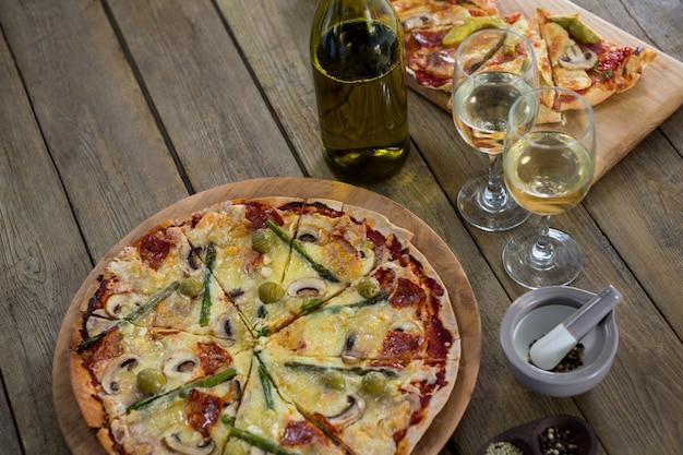 와인 잔과 재료를 곁들인 이탈리아 피자